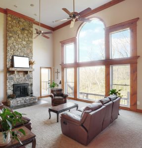 Traditional living room interior with a high ceiling and large windows. Square format.